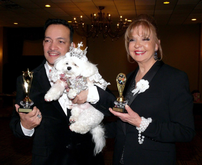 Pet Couturier Anthony Rubio holding Maltese Bella Mia and Rose Ann Bolasny  after  being awarded the Designer Of The Year Award and Best Dressed Dog Award  at the New York Pet Fashion Show (Photo by Richard Alicea)