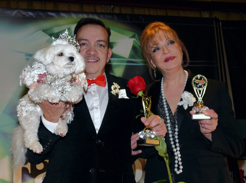 Pet Couturier Anthony Rubio holding Maltese Bella Mia and Rose Ann Bolasny  after  being awarded the Designer Of The Year Award and Best Dressed Dog Award at the New York Pet Fashion Show Photo by Richard Alicea