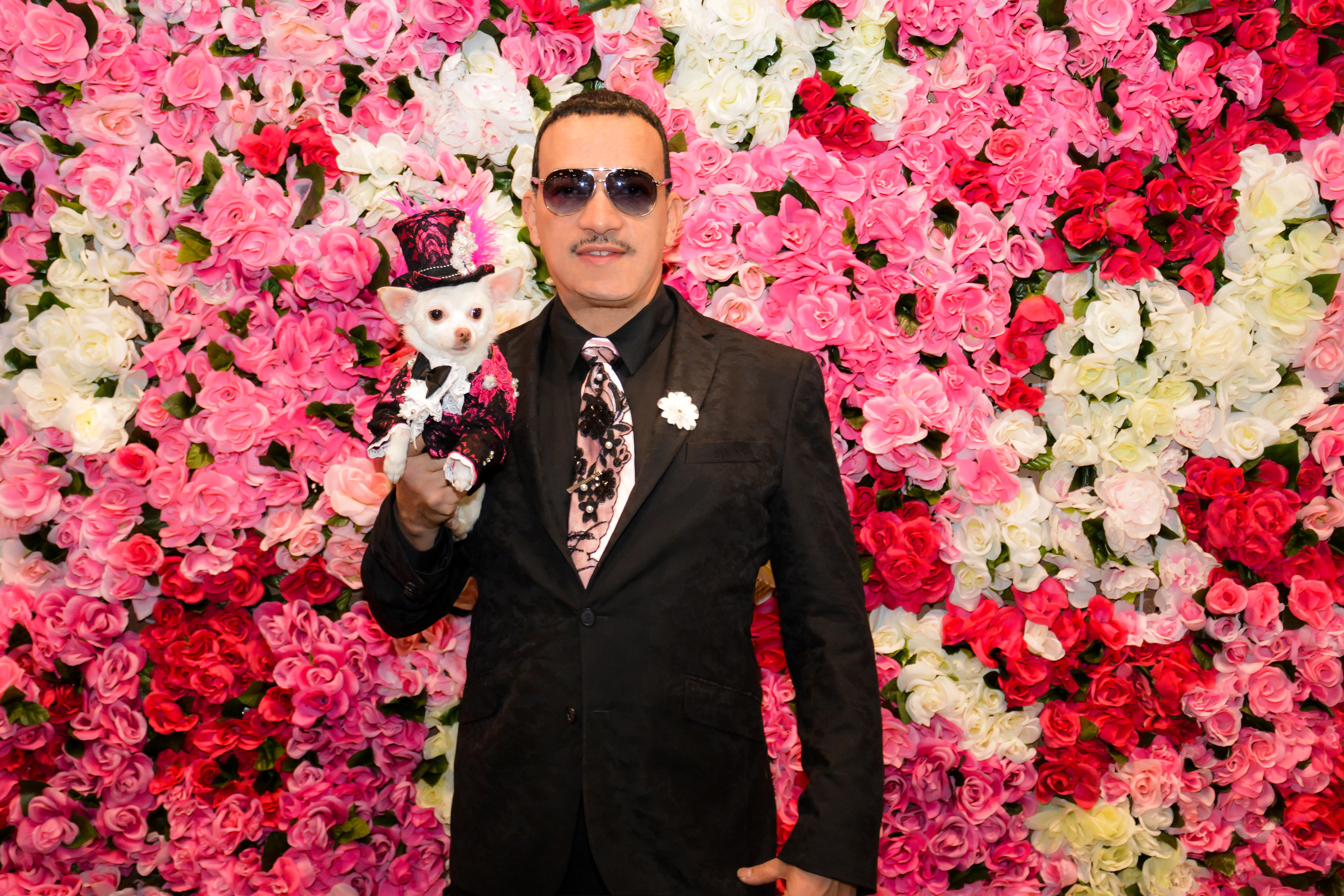 Spring Is In The Air! Pet Couturier Anthony Rubio with his Chihuahua Kimba wearing a pink with black lace overlay tuxedo and matching top hat created by Anthony Rubio.